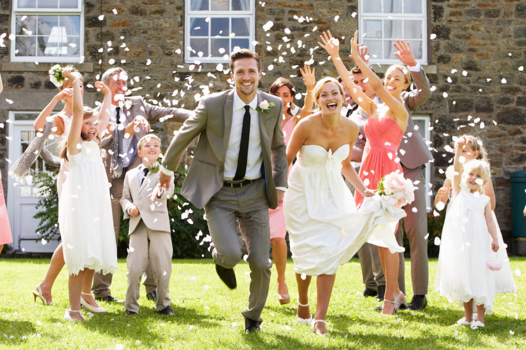 Confetti being thrown to bride and groom