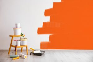 half-painted wall with some painting supplies