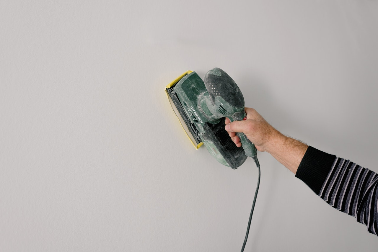 person polishing the dry wall