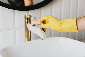 person scrubbing the faucet