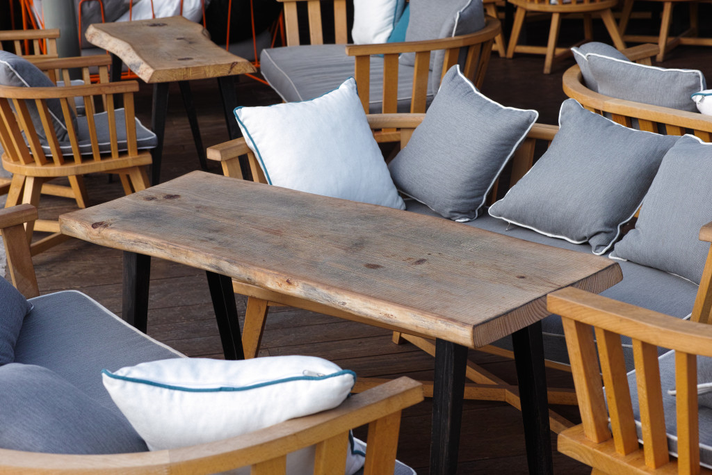 Wooden tables and chairs with pillows in street cafe
